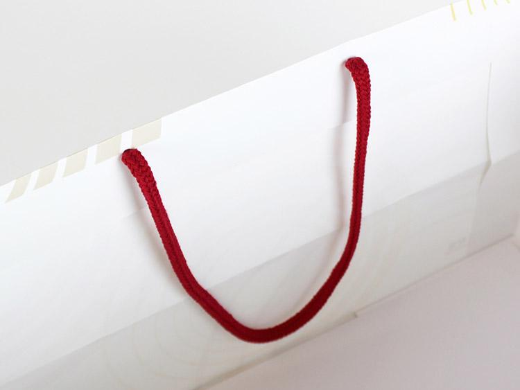 赤いアクリルスピンドル紐の付いた紙袋